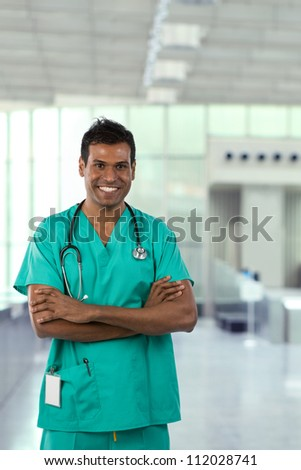 Male Indian Doctor wearing Green Scrubs in modern hospital. - stock photo