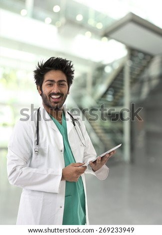 Male Indian doctor wearing lab coat and green Scrubs & stethoscope. - stock photo