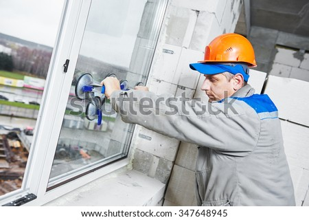 male industrial builder worker at window installation in building construction site - stock photo