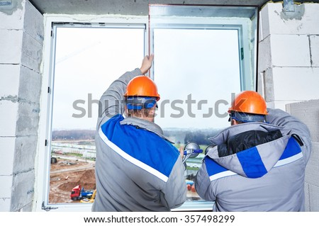 male industrial builders worker at window installation in building construction site - stock photo