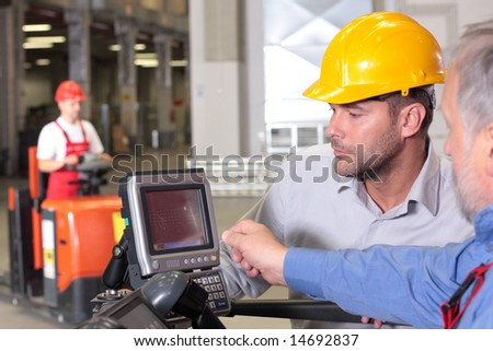 male inspector looking at screen with operator in warehouse - stock photo