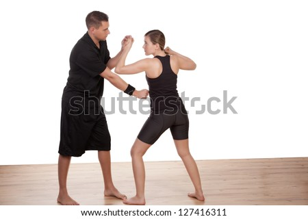 Male instructor teaching a barefoot young woman kick boxing demostrating how to block a punch and penetrate the opponents defenses - stock photo