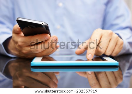 male is using smart mobile phone and tablet computer at the same time - stock photo