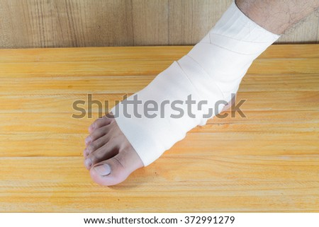 male is wrapping his Foot injury with bandage. - stock photo