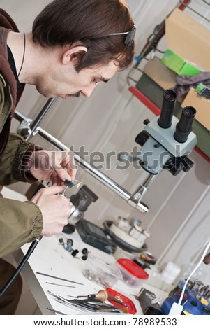 Male jeweller is working at jeweller's workshop