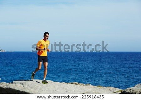 Male jogger in fluorescent t-shirt runs over sea rocks at morning training outdoors - stock photo
