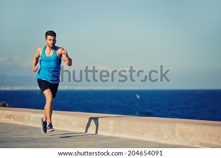 Male jogger with high speed running along the sea on the pier, athletic sportsman on the evening run, fitness and healthy lifestyle concept