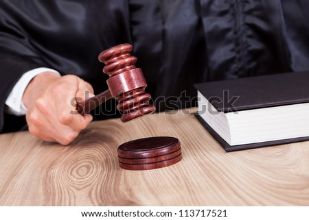 Male Judge In A Courtroom Striking The Gavel - stock photo