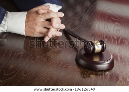 Male Judge Rests Folded Hands Behind Gavel with American Flag Reflection on Wooden Table. - stock photo