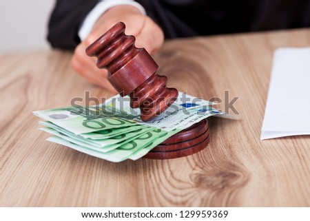 Male Judge Striking The Gavel Euro Note In A Courtroom - stock photo