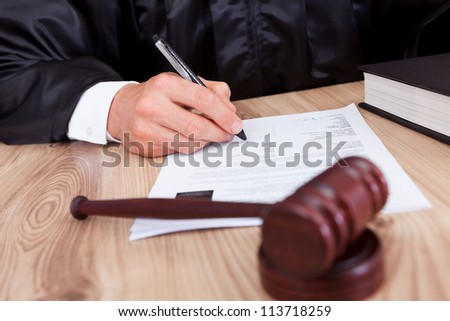 Male Judge Writing On Paper In Courtroom - stock photo