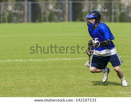 Male Lacrosse Player holding stick on a grass field with copy space - stock photo
