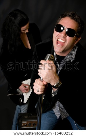 Male lead singer with retro mic and female guitar player in background - stock photo