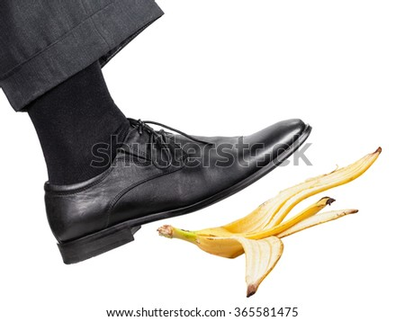 male leg in the right black shoe slips on a banana peel isolated on white background - stock photo