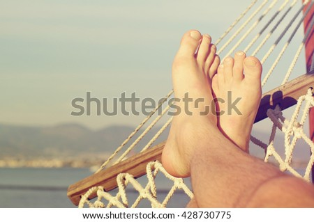 Male legs in a hammock on the beach against the sea in a summer sunny day. Holiday by the sea - stock photo