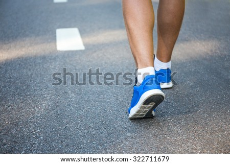 male legs in running shoes outside on asphalt road - stock photo