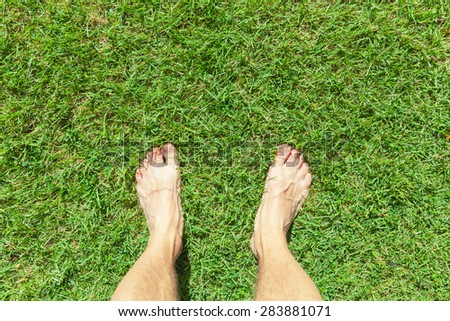 Male legs stand on a green grass lawn