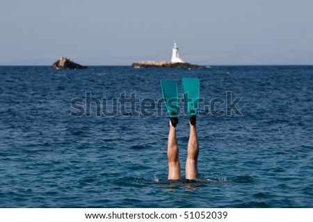male legs with flipper and lighthouse in background - stock photo
