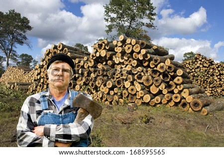 male lumberjack standing in front of a large stack of logs - stock photo