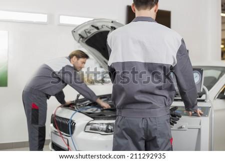 Male maintenance engineers examining car in workshop - stock photo