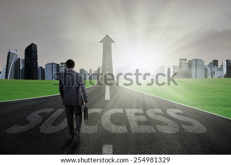 Male manager carry briefcase and walk on the road going up as an arrow with a success text - stock photo