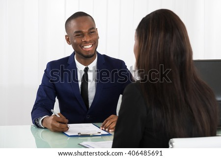 Male Manager Interviewing A Young Female Applicant In Office - stock photo