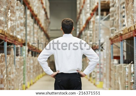 male manager man standing in big modern warehouse with back towards viewer - stock photo