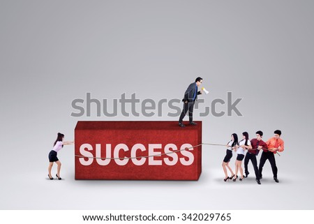 Male manager use a megaphone to command his team and remove an obstacle with a text of success - stock photo