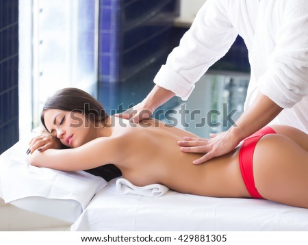 Male massage therapist in white uniform massing with hands attractive woman with sexy naked body and buttocks lying on couch - stock photo