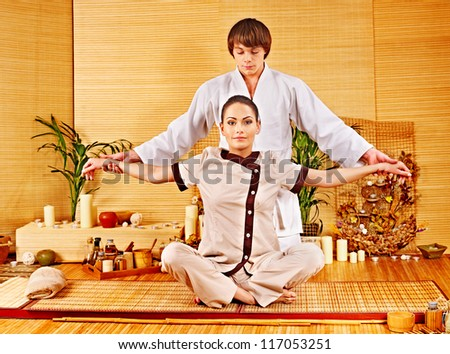 Male masseur doing massage young woman in bamboo spa. - stock photo