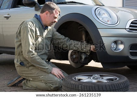 Male mechanic at a car garage fixing a wheel