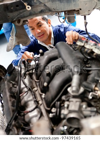 Male mechanic at a garage fixing a cars engine - stock photo