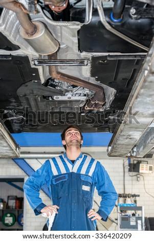 Male mechanic examining under the car at repair garage - stock photo