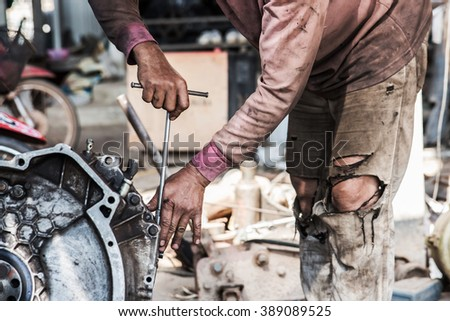 Male mechanic fixing a car engine.
