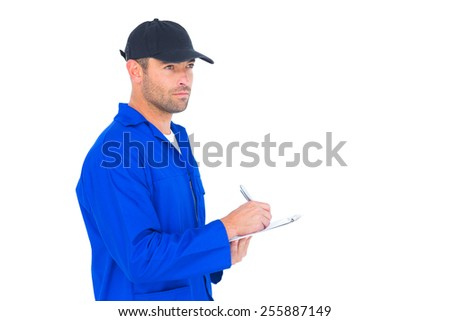 Male mechanic in blue overalls writing on clipboard over white background - stock photo
