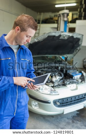 Male mechanic using digital tablet with car in background - stock photo