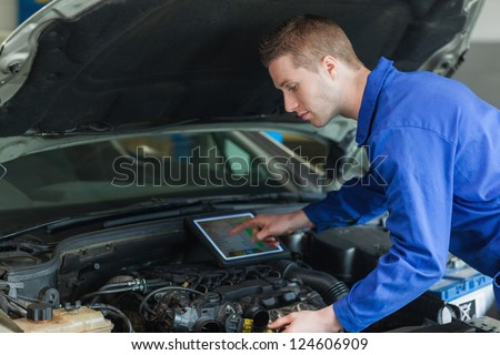 Male mechanic using tablet pc while examining car engine - stock photo