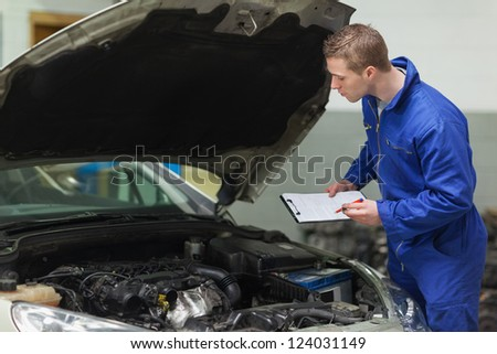 Male mechanic with clipboard examining car engine - stock photo
