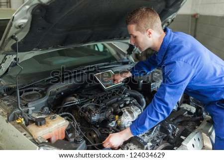 Male mechanic with digital tablet repairing car engine - stock photo