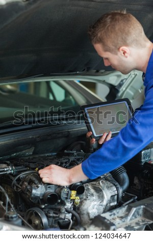 Male mechanic with tablet pc repairing car engine