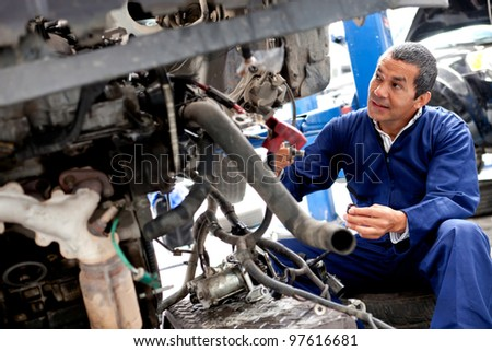 Male mechanic working on a car at a repair shop - stock photo