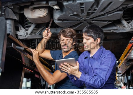 Male mechanics using digital tablet while working under lifted car at auto repair shop - stock photo
