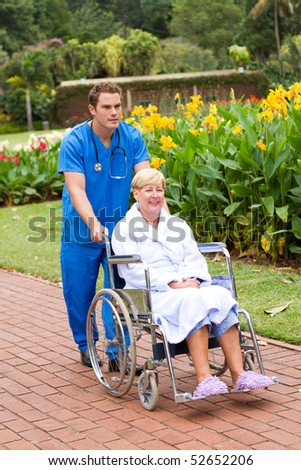 male medical doctor or nurse pushing senior patient on wheelchair outdoors for some fresh air