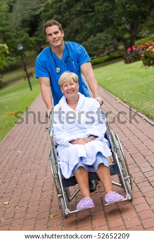 male medical doctor or nurse pushing senior patient on wheelchair outdoors for some fresh air - stock photo