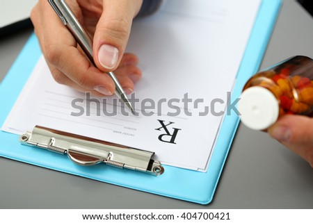 Male medicine doctor hand hold jar of pills and write prescription to patient at worktable. Panacea and life save, prescribing treatment, legal drug store concept. Empty form ready to be used - stock photo