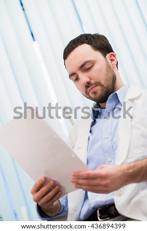 Male medicine doctor hand holding papers. Ward round, patient visit check, medical calculation and statistics concept. Physician ready to examine patient - stock photo