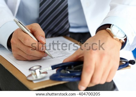 Male medicine doctor hand holding silver pen writing something on clipboard closeup. Ward round, patient visit check, medical calculation and statistics concept. Physician ready to examine patient - stock photo