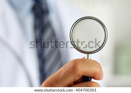 Male medicine doctor hand holding stethoscope head closeup in front of his chest. Healthy heart, eating and lifestyle, physician ready to examine patient, physical and disease prevention concept - stock photo