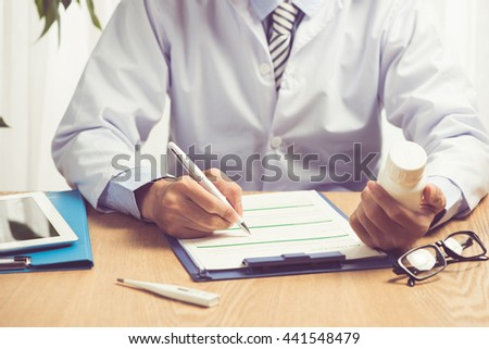Male medicine doctor hands hold jar of pills and type something on laptop computer keyboard.  - stock photo