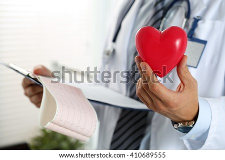Male medicine doctor hands holding red toy heart and cardiogram chart on clipboard closeup. Cardio therapeutist, physician make cardiac physical, heart rate measure, arrhythmia concept - stock photo